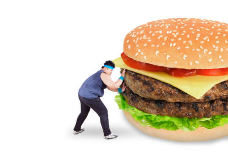 Healthy life concept. Overweight man refused to eat a big burger and pushing it photo