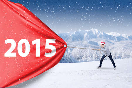 Young man wearing christmas hat and pulling number 2015 on a big banner photo