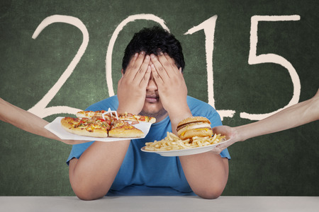 Healthy life plan. Overweight person avoiding to eat junkfood in 2015 photo