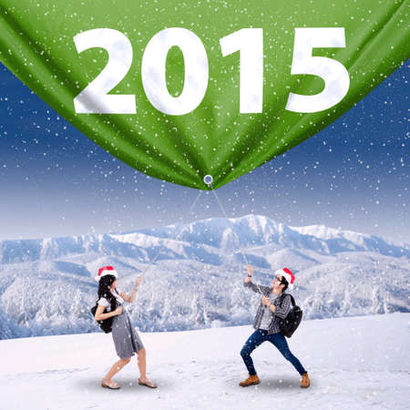Student wearing christmas hat and pulling number 2015 in winter photo