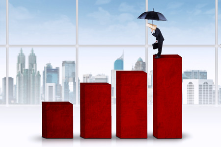 Anonymous businessman holding umbrella, standing on business chart and looking at the past photo