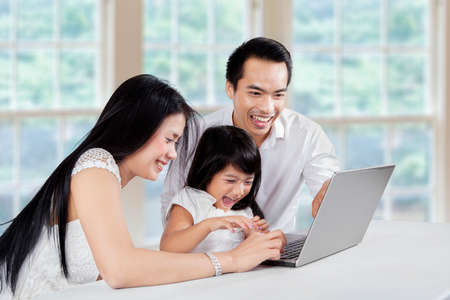 Three member of happy family using laptop computer for browsing internet photo