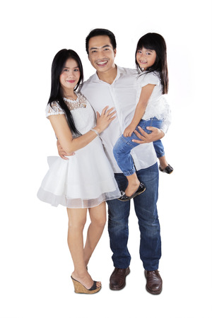 スタジオで若いアジア家族立って、カメラに笑顔 写真素材