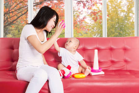baby sit: Happy mother playing with her baby and toys on sofa at home Stock Photo