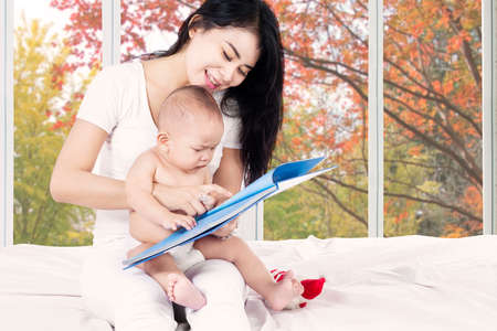 hold: Cute baby read a story book with mother on bedroom