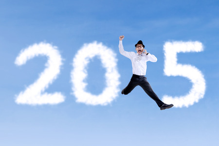 Happy businessman jumping on the sky while calling and forming number 2015 photo