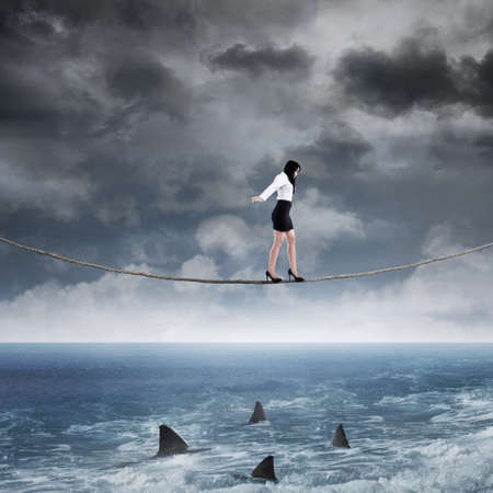 business metaphor: Concept of business risk with businesswoman walk on the rope above sea Stock Photo