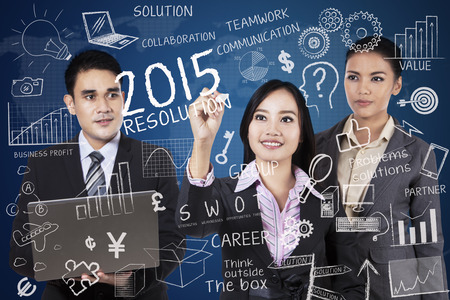 successful business: Three business people discussing the resolutions in 2015 Stock Photo