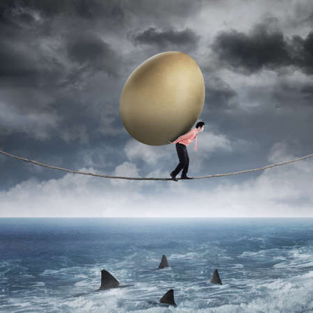 savings problems: Asian businessman carrying golden egg while walking on the rope above sea Stock Photo