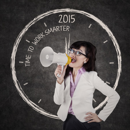 smarter: Asian businesswoman shouting with megaphone and give order to work smarter in 2015