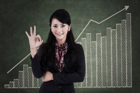 good investment: Happy businesswoman making an ok sign - in front of business chart