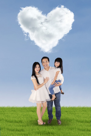heart under: Three member of happy little family standing on the meadow under cloud shaped heart