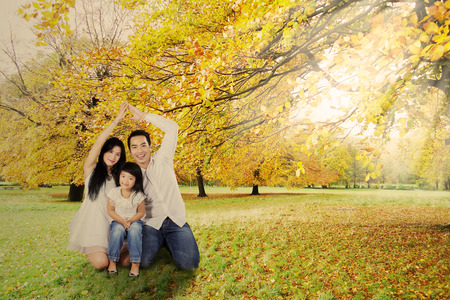 fall protection: Father and mother made a home shape with their hands to protect their child
