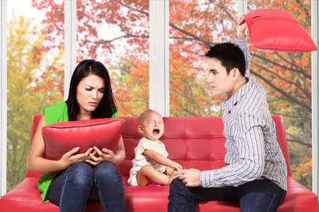 Young hispanic couple quarreling with their child crying on sofa photo