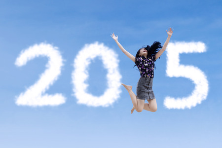 Asian woman jumping on the sky expressing freedom and forming number 2015 photo