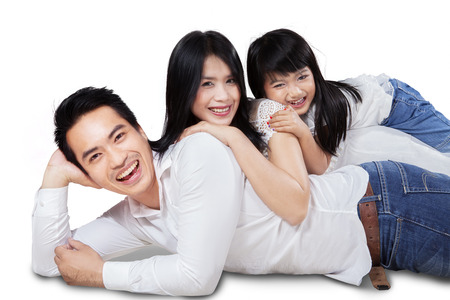 Cheerful family smiling at camera while lying and cuddling in studio