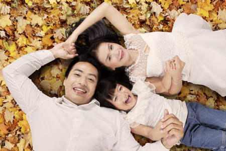 High angle view of asian family lying on autumn leaves, shot outdoors photo