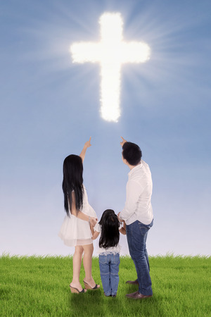 worship hands: Three member of happy family pointing at cloud shaped cross on the meadow