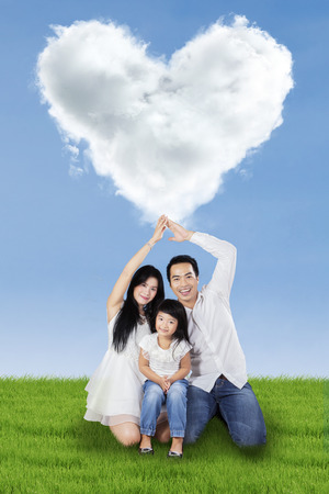 Young asian family sitting on meadow under cloud shaped heart photo