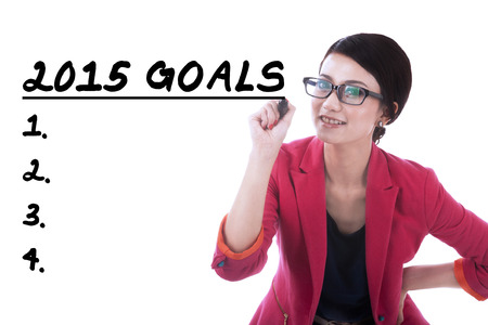 Young hispanic businesswoman makes her goals in 2015, isolated over white background photo