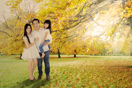 Happy little family standing under autumn tree enjoying holiday photo