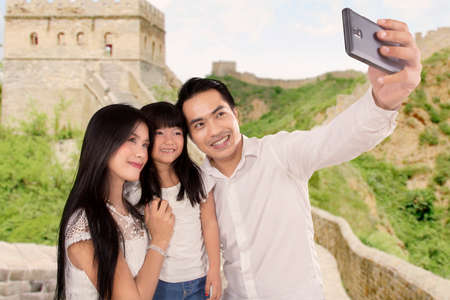 Three of member happy family taking self portrait together in Great Wall of China Stock Photo