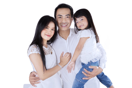 Young happy family wearing white clothes and smiling at camera in studio photo