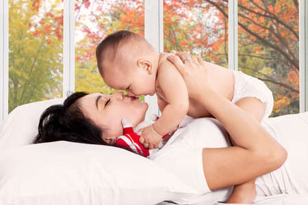Mother kiss her baby girl on bedroom with autumn tree background on the window photo