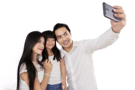 Gelukkige familie het nemen van foto samen in de studio, geïsoleerd op witte achtergrond Stockfoto