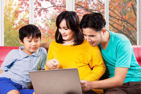 Father, mother, and child using laptop computer on sofa at home with autumn tree background photo