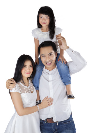 Cheerful family standing in studio while smiling at camera, isolated over white photo