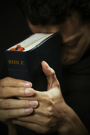 Portrait of man praying with bible photo