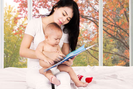 Young mother and her baby read a story book on the bedroom at home photo