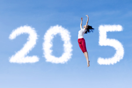 Attractive woman dancing on the sky and forming number 2015 photo
