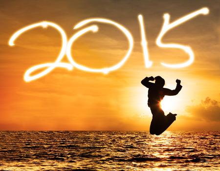 january sunrise: Silueta de mujer alegre que salta en la playa de celebrar el a�o nuevo 2015