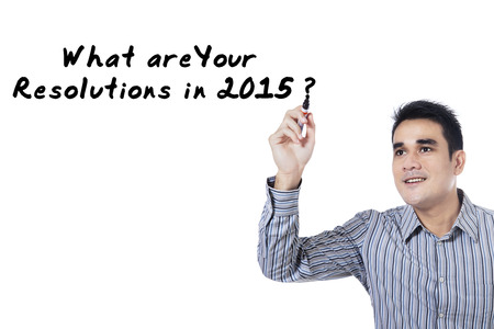 Hispanic person writes a question about resolutions in 2015 photo