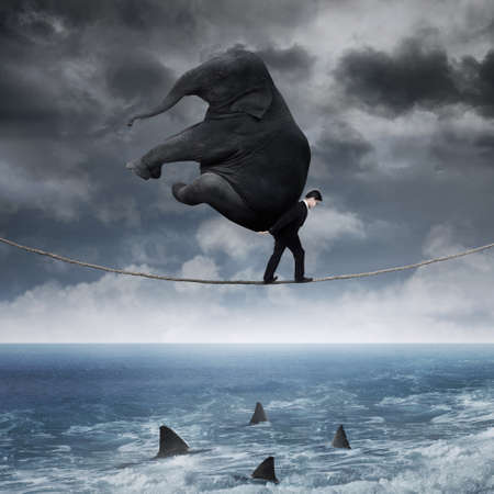 heavy risk: Business person carrying an elephant and walk on the rope above sea