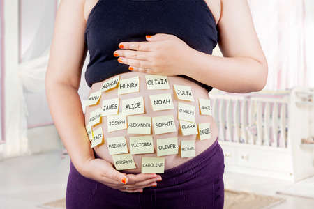 my name is: Close up of pregnant belly with baby names choices on woman belly, shot in bedroom