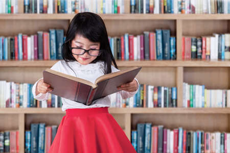 literature: Asian little girl reads book seriously in library with bookcase background Stock Photo