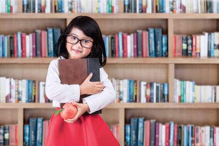 niños en la escuela: Niña adorable que se coloca en biblioteca mientras sostiene un libro y la manzana