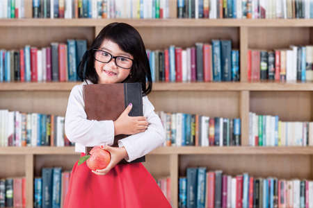 školní děti: Rozkošná holčička stojící v knihovně, zatímco drží knihu a apple Reklamní fotografie