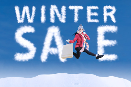 Winter sale clouds and woman jumping happily with shopping bag photo