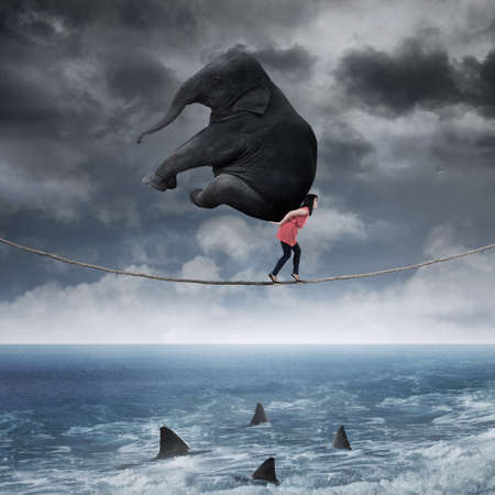 Asian woman carrying an elephant while walking on the rope above the sea photo