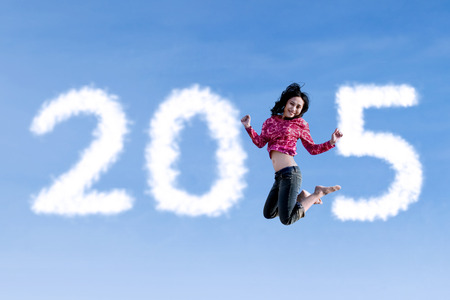 Hispanic woman jumping on the sky and forming number 2015 photo