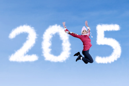 Happy woman wearing sweater and jump to forming number 2015 photo