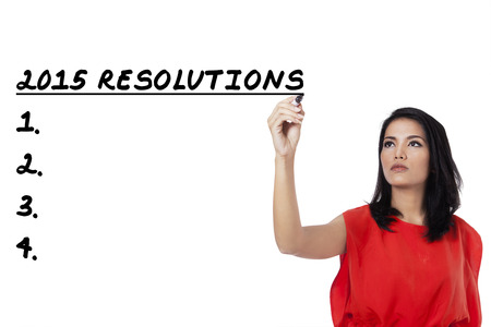 Young asian woman writes a list of resolutions in 2015, isolated over white background photo