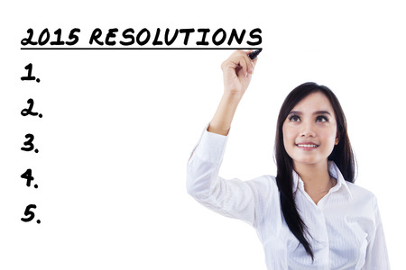 Beautiful businesswoman writes resolutions list in 2015 photo