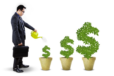 watering pot: Young businessman using watering can to nurture the money trees