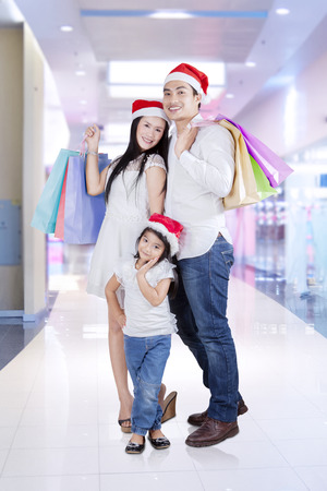 Happy family posing and smiling on camera with shopping bags in the mall photo