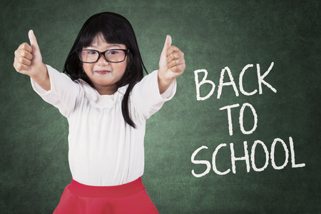 back to school kids: Cute little asian girl give thumbs-up in classroom, symbolizing happiness back to school